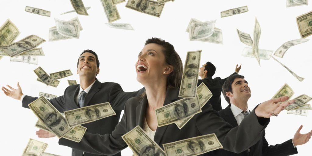 Multi-ethnic businesspeople under rain of money