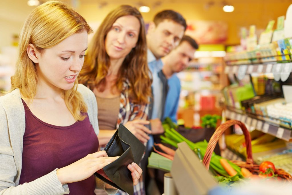 33921116 - embarrassed woman looking for money in her wallet at supermarket checkout