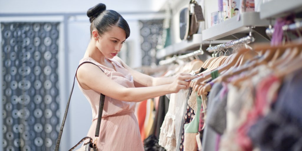lady browsing through a clothes rail of dresses