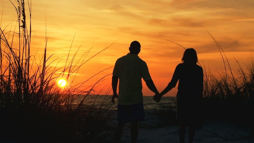 stock-footage-young-ethnic-couple-silhouette-holding-hands-watching-sunset-on-beach-vacation-loving-couple-holding-hands-1526156534